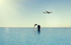 Młoda kobieta w basenie na dachu w tle samolot i księżyc Kobieta w pływackim basenie na dachu Zdjęcia Stock