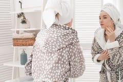 Młoda kobieta w bathrobe blisko w domu lustrze Ranek rutyna fotografia royalty free