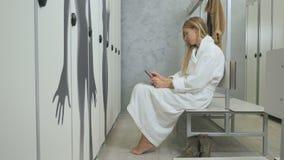 Młoda kobieta w bathrobe siedzi na ławce w przebieralni i używa smartphone zbiory wideo