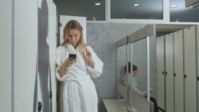 Młoda kobieta w bathrobe używa smartphone w przebieralni zbiory wideo
