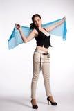 Młoda kobieta w beżu dyszy, czerni kamizelka z błękitnym szalikiem Zdjęcia Stock