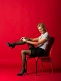 Młoda kobieta w białej czerni spódnicie i bluzce koryguje pończochę Obrazy Stock