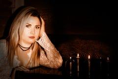 Młoda kobieta w białej przejrzystej sukni stending blisko czarnego candels, wróżby i czarnej magii pojęcia, Zdjęcia Stock