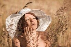 Młoda kobieta w białym kapeluszu cieszy się słońce Zdjęcie Royalty Free