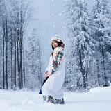 Młoda kobieta w biel sukni haftującej z kwiecistym projektem, kolorowa chustka z błękitną naramienną torbą fotografia royalty free