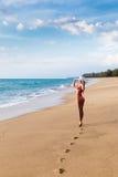 Młoda kobieta w bikini w kapeluszu na piaskowatej plaży Zdjęcia Stock