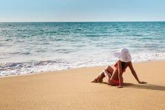 Młoda kobieta w bikini w kapeluszu na piaskowatej plaży Zdjęcia Royalty Free
