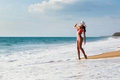 Młoda kobieta w bikini w kapeluszu na piaskowatej plaży Obrazy Stock
