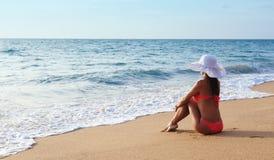 Młoda kobieta w bikini w kapeluszu na piaskowatej plaży Zdjęcie Stock
