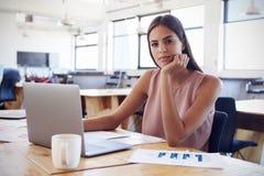 Młoda kobieta w biurowych używa laptopów spojrzeniach kamera Obraz Royalty Free
