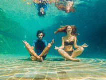 Młoda kobieta w czarnym bikini i mężczyzna w joga ustawiamy podwodnego w nurkowym akwarium, pełny ciało strzał, frontowy widok obraz royalty free
