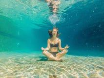 Młoda kobieta w czarnym bikini w joga pozyci podwodnej w nurkowym akwarium, pełny ciało strzał, frontowy widok Zdjęcie Stock