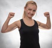 Młoda kobieta w czarnym podkoszulek bez rękawów z dumbbells obraz stock