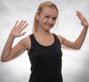 Młoda kobieta w czarnym podkoszulek bez rękawów z oba rękami otwiera zdjęcia stock