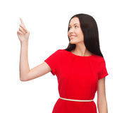 Młoda kobieta w czerwieni smokingowej wskazujący jej palec obrazy royalty free