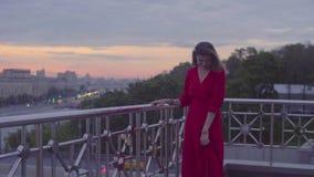 Młoda kobieta w czerwieni sukni jest chodzącym pobliskim parapet zbiory wideo