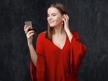 Młoda kobieta w czerwieni sukni jest przyglądająca mały kieszeni lustro wewnątrz Zdjęcia Stock