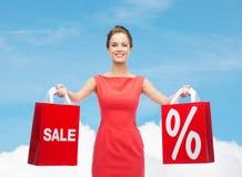 Młoda kobieta w czerwieni sukni z torba na zakupy Zdjęcie Stock