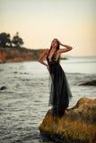 Młoda kobieta w długich czerni sukni stojakach na skale morzem Obrazy Stock