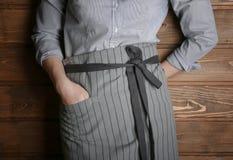 Młoda kobieta w fartuch pozyci na drewnianym tle zdjęcie stock