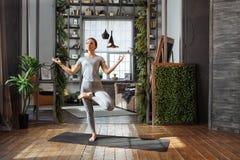 Młoda kobieta w homeware ćwiczy balansową joga pozę na dywanie w jej comfy sypialni Obrazy Royalty Free