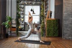 Młoda kobieta w homeware ćwiczy balansową joga pozę na dywanie w jej comfy sypialni Fotografia Stock