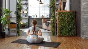 Młoda kobieta w homeware ćwiczy balansową joga pozę na dywanie w jej comfy sypialni Zdjęcie Stock