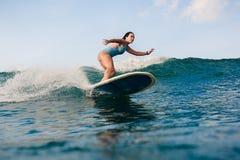 Młoda kobieta w jaskrawym bikini surfingu na desce w oceanie zdjęcie royalty free