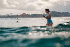 Młoda kobieta w jaskrawym bikini surfingu na desce w oceanie obrazy stock
