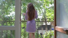 Młoda kobieta w jedwabniczym bathrobe iść balkon hotel z filiżanką wewnątrz i zwroty kamera na tle zieleni drzewa zbiory wideo