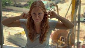 Młoda kobieta w jej mieszkaniu cierpi od hałasu wytwarzającego budową na zewnątrz okno zbiory wideo
