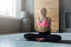 Młoda kobieta w joga klasie, relaksuje przyrodnią lotos pozę fotografia royalty free