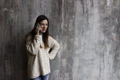 Młoda kobieta w kardiganu beżowych stojakach przeciw szarości ścianie i obrazy stock