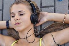 Młoda kobieta w koszulce z słuchającą muzyką i kłamstwami na bruku zdjęcia royalty free