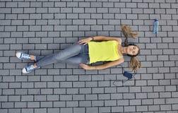Młoda kobieta w koszulce z słuchającą muzyką i kłamstwami na bruku zdjęcia stock
