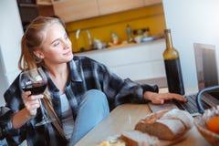 Młoda kobieta w kuchennym pije wina dopatrywania filmu w domu zdjęcia royalty free