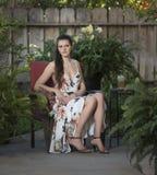 Młoda kobieta w lato sukni, siedzi w łozinowym krześle zdjęcie stock