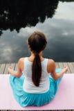 Młoda kobieta w lotosowej pozyci ćwiczy joga w lesie obok rzeki siedzieć dalej matuje drewnianego molo Fotografia Stock
