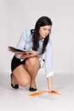 Młoda kobieta w mini spódnicie i bluzce kuca, wzrasta od g zdjęcia royalty free