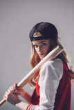 Młoda kobieta w nakrętki mienia kiju bejsbolowym i patrzeć kamerę Obraz Stock