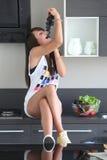Młoda kobieta w nowożytnej kuchni, je wiązkę winogrona Zdjęcie Stock
