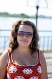 Młoda kobieta w okularach przeciwsłonecznych blisko stawu na słonecznym dniu Zdjęcia Stock