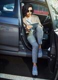 Młoda kobieta w okularach przeciwsłonecznych z pastylki obsiadaniem w samochodzie obrazy stock