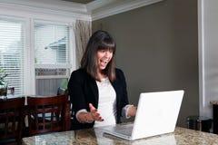 Młoda kobieta w ona domowy szczęśliwie patrzeje komputer Obraz Royalty Free