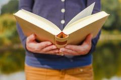 Młoda kobieta w parkowego mienia otwartej książce Obraz Stock