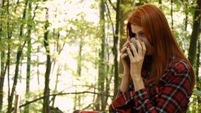 Młoda kobieta w parku lub w lasowej pije herbacie od filiżanki lub kawie zdjęcie wideo