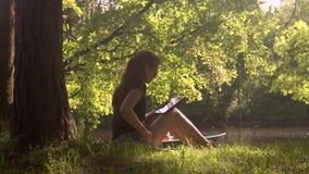 Młoda kobieta w parku używa smartphone i pastylkę zbiory