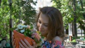 Młoda kobieta w pięknym smokingowym odprowadzeniu w parku z bukietem kwiaty, zakończenie Piękny uśmiech zbiory