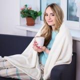 Młoda kobieta w piżamach zawijać w powszechnym obsiadaniu w żywym pokoju obraz stock