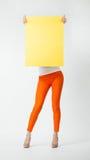 Młoda kobieta w pomarańcze dyszy mienie plakata pusty żółty chować Fotografia Royalty Free